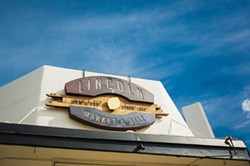 MARKET FRESH:  San Luis Obispo metal wizard Jory Bringham created Lincoln Market's eye-catcing sign as well as the large community table found inside the eclectic hangout, grocery, and deli. - PHOTO BY KAORI FUNAHASHI
