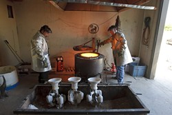 Alphonso Sepeda, left, and John Kemple, right, prepare to pull out the crucible containing the molten bronze. - PHOTO BY STEVE E. MILLER