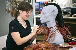 WAR NECKLACE :  Weta costume technician Claire Prebble assembles a war necklace for Tsu'tey, a character from James Cameron's Avatar. While the version you see onscreen was computer generated, Weta typically makes such items through traditional methods first. Then, 3-D modeling artists copy the physical item as closely as possible. - PHOTO BY STEVE UNWIN