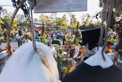 GRIM GREETERS:  Two skeleton scarecrows tower above the Scarecrow Festival's kick-off party, held at Cambria Nursery & Florist, where the judges' selections for best scarecrows are announced. - PHOTO BY KAORI FUNAHASHI