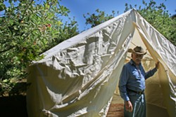 CAMP OUT :  SLO-based glamping outfitter Whereabout has partnered with FARMstead ED and Windrose Farms to present bohemian-style camping during the farm's annual Heirloom Tomato Fest slated for Sept 20-21 in Paso Robles. Pictured, Windrose Farm owner Bill Spencer checks out the canvas tent in the days leading up to the celebration of all things big, red, and juicy. - PHOTO BY HAYLEY THOMAS