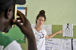 TESTING:  Peace Corps volunteer Claire Dal Nogare points to the letters of vision test on the wall in a makeshift medical clinic in Sabana Larga. Dal Nogare and four other Peace Corps volunteers based in the Dominican Republic helped translate in Spanish and English during the latter part of the week. - PHOTO BY CAMILLIA LANHAM