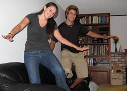 RIDING THE COUCH :  Kate Harrison and Nik Goodell barely grumbled when asked to pretend surfing on a couch. Harrison put up her house for the night and Goodell was looking for a place to stay before going back to Santa Cruz - PHOTO BY PATRICK HOWE