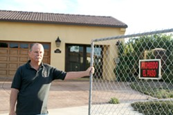 GATED COMMUNITY:  Maria Vista Estates resident Aaron Adams bought his $700,000 home in 2007, thinking he'd found a place to retire but he now stands watch for vandals and burglars intent on raiding vacant homes in his neighborhood for appliances. - PHOTO BY JEREMY THOMAS