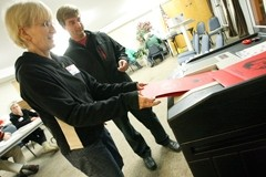 THE ACT :  Poll worker Karen Poling helps Ken Pettit complete voting on Election Day. Few problems were reported at area polling places. - PHOTO BY STEVE E. MILLER