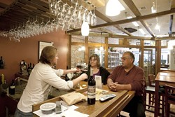 FOR A GOOD TIME :  Rick Cronkhite recently poured some vino for Ralph and Dolores Vasquez at the newly opened Central Coast wines. - PHOTO BY STEVE E. MILLER