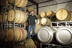 MORE FUN THAN A BARREL OF MONKEYS:  Ryan Deovlet, winemaker, stands amongst some of his aging barrels at his Deovlet winemaking facility in San Luis Obispo. - PHOTO BY STEVE E. MILLER