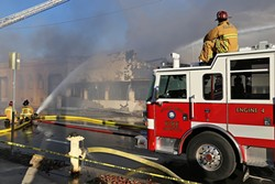 ASHES TO ASHES :  SLO firefighters worked for hours to put out an aggressive fire that gutted a popular novelty store on Higuera Street Dec. 26. The cause of the blaze has not yet been determined. - PHOTO BY DYLAN HONEA-BAUMANN