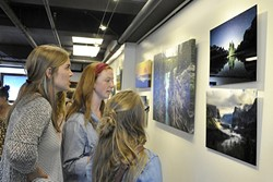 """INSPIRED:  Alisha Ostby, Olivia Essen, and Gigi Greene check out Burkard's photos. Essen said before she saw his photography, she thought anyone could take a good photo. """"It's amazing, quite honestly, he's one of the photographers that pushed me into looking deeper into photography,"""" she says. - PHOTO BY CAMILLIA LANHAM"""