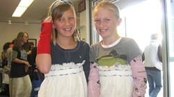 YOUNG SEAMSTRESSES :  With the help of volunteers, friends Sabina Zink and Gretta Carlson fashioned differently styled dresses from the same curtain cloth. - PHOTO BY NICK POWELL
