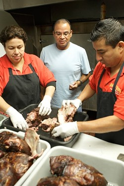 PORK-TASTIC! :  Cowell (center) and colleagues Norma Moreno and Ricardo Perez are ready to pull pork for their renowned sandwiches. - PHOTO BY KATHY MARCKS HARDESTY