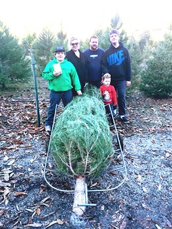 GO BIG OR GO HOME:  The Wood boys—Andrew, Evan, and Logan (from left to right)—and Merissa and Tim James (center), picked a 10-foot tall Monterey Pine that the kids were convinced was the perfect fit. Good thing they have vaulted ceilings at home. - PHOTO BY JONO KINKADE