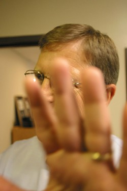 NO PHOTOS :  District Attorney Gerald Shea fends off a New Times photographer prior to a 2003 interview. - FILE PHOTO BY CHRISTOPHER GARDNER