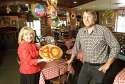 """TOP THIS! :  Bernadette """"Bernie"""" Donakowski—pictured here with her son Ryan, who manages Del's—is celebrating 40 years of bringing pizza and other delicious Italian food to the county. - PHOTO BY STEVE E. MILLER"""
