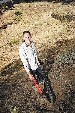 GRAYWATER TO GARDEN :  Mikel Robertson has installed a legal graywater system to irrigate a future orchard on his rural property. The $180 county permit he bought for the system will no longer be required after Aug. 4. - PHOTO BY STEVE E. MILLER