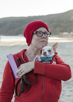 LIFE AQUATIC, AND CANINE:  Newlywed Aileen Manley, wearing the red beanie that has become the trademark of this ridiculous event, protected her love Taco from the elements. - PHOTO BY COLIN RIGLEY