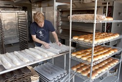 FERMENTED EDIBLES:  Back Porch Bakery started out selling products literally on a porch, but now co-owner Dan Berkeland (prepping baguettes for the oven) makes many different types of bread for a variety of restaurants around the county. - PHOTO BY STEVE E. MILLER