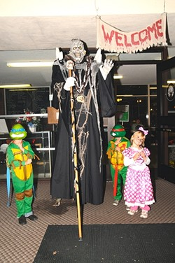 """WORLD'S TALLEST GREETER!:  In addition to the haunted house, kids can get photos with scary characters and win prizes from carnival games. - PHOTO BY BETTY """"DOC"""" O'CONNOR"""