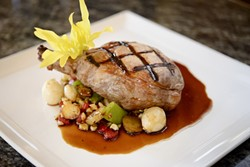 PLUMP PIGS:  On the dinner menu, one can order this grilled Berkshire pork chop with grilled corn succotash and red eye gravy. - PHOTO BY STEVE E. MILLER