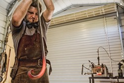 HOT STUFF:  Using his anvil to steady the steel, Randolph slowly curves the end of it up. - PHOTO BY KAORI FUNAHASHI