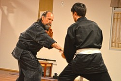 "EMPOWERMENT:  Jim Risinger goes blow-for-blow with a student. He and sensei Kenshin ""Neil"" Miyamoto teach tai chi, karate, and ninjitsu - at the Rising Sun Martial Arts Academy in Santa Maria. - PHOTO BY DAVID MINSKY"