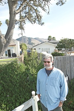FENCES, NEIGHBORS :  Tim Page of the citizen group Save Our Access Path stands in front of homeowner Mark Yandow's house. The two are working on a settlement to reopen a long-closed path to the beach. - FILE PHOTO