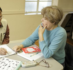 ONE LESSON AT A TIME :  Mary Kleeman works with a Chinese student whose lessons are frequently interrupted by his return trips to China. - PHOTO BY STEVE E. MILLER