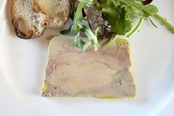 PLATED: :  A slice from a terrine of foie gras is strong enough to be served on its own, accompanied - by greens and a toasted baguette round. - PHOTO BY STEVE E. MILLER