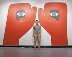 OPPOSABLE ART :  Geoff McFetridge stands inside one of his large-scale paintings, currently on view at Cal Poly University Art Gallery. Though McFetridge's designs have appeared in music videos, on shoes and skateboards, and in national ad campaigns, he's still got one foot firmly rooted in the world of fine art. - PHOTO BY STEVE E. MILLER