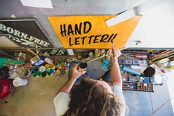 BETWEEN THE LINES:  Bond retreats to his colorful Templeton garage/workspace, cranks the country, and hand paints signs till his knuckles ache. - PHOTO BY KAORI FUNAHASHI