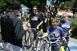 BLESSED! :  The Jiminez family—(left to right) Mario, Sevryn, and Sherry—collectively get their bikes blessed. Sherry owns Salon 544 and organized the free family event. - PHOTO BY GLEN STARKEY