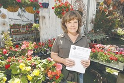 CERTIFIED :  Hope Merkle holds the certificate proclaiming that the Los Osos Valley nursery she manages is cleared of Light Brown Apple Moth. Five of the invasive moths were found in Los Osos, prompting the state to issue a quarantine. - PHOTO BY STEVE E. MILLER