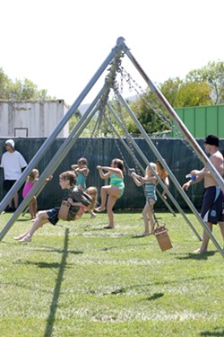 SWINGERS :  Kids were everywhere, swinging, climbing, and tumbling through the grassy playground area by the pool. - PHOTO BY GLEN STARKEY