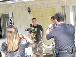 POSING :  Police aided and abetted publicity surrounding the escape of a 23-foot-long python, but the fallout has been a problem for owner Brandon Dennis (with snake) and his roommates, including Elliot Barrington (left). - FILE PHOTO