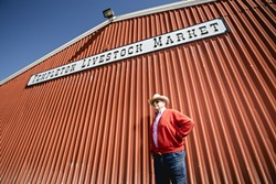 THE BIG RED BARN:  Dick Nock stands before the Templeton Livestock Market in February. - PHOTO BY TOM FALCONER