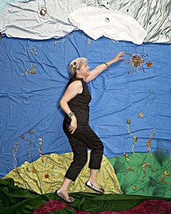 REACH FOR THE SKY :  Jeweler Debra Jurey grasps the sun in a garden of her own making, in the first of four experimental New Times Autumn Arts photo shoots. - PHOTO BY STEVE E. MILLER