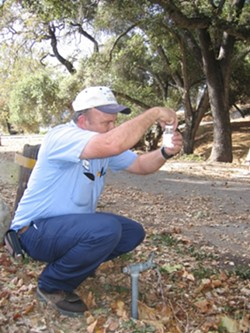 FAUCET FLOW :  Drinking water is tested regularly, even at Lopez Lake campground, where Water Systems Operator Mark Woelfle fills a sample bottle. - PHOTO BY KATHY JOHNSTON