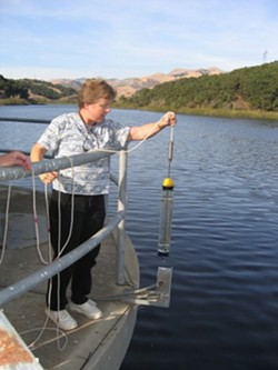 TESTING THE WATERS :  Lopez Lake water spends 30 days in the terminal reservoir off Orcutt Road, where Water Systems Chemist Lisa Wallender grabs samples at various depths. - PHOTO BY KATHY JOHNSTON