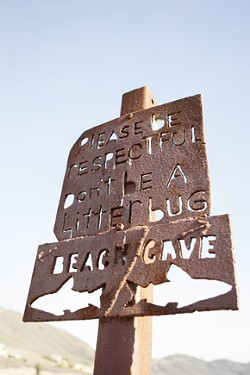 DON'T BE A LITTERBUG :  A handmade sign above the cove offers directions, as well as a little insight into local customs. The beach functions almost without incident, and is maintained by the efforts of its regular sunbathers. - PHOTO BY STEVE E. MILLER