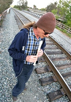 PUBLIC FLUTING :  Eric Cletsoway recently walked the section of tracks where he was arrested for trespassing over Mardi Gras weekend. The flautist was injured by police during the arrest. - PHOTO BY CHRISTOPHER GARDNER