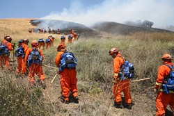 HEAT OF THE MOMENT :  An inmate fire crew, led by California Department of Forestry officers (in the yellow suits), worked to safeguard a burned site from reigniting on Cuesta Grade. - PHOTO BY JESSE ACOSTA