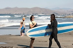 Surf Mama Erin Hadley is all smiles as another mama heads into the ocean. - PHOTO BY STEVE E. MILLER