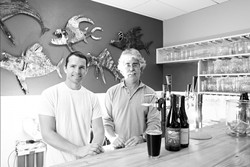 RAISING THE BAR :  Mark London (right) opened SLO Down Pub in Arroyo Grande. SO-AND-SO (left) built the bar out of a fallen pine tree. The pub features locally produced alcohol, recycled fixtures, and a green heart. - PHOTO BY STEVE E. MILLER