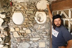 A MAN'S HOME IS HIS CASTLE :  Mike O'Malley demonstrates how Nitt Witt Ridge reflects its creator's eccentricity, like Hearst Castle a-ways up Highway 1, but with more toilet seat de cor. - PHOTO BY STEVE E. MILLER