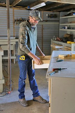 BUILDING HOME:  Sunny Acres resident David Dieter has a background in the cabinet industry. Since he arrived at the facility four months ago, he's remodeled the wood shop. Dieter said he's battled alcoholism in his life, but because he's got so much to do at Sunny Acres, he hasn't been drinking. The sober living facility is in the process of trying to get its zoning changed so more people can get off the streets and into a bed on the property. - PHOTO BY DYLAN HONEA-BAUMANN
