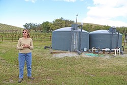 TANKED:  Sue Luft stands beside her water tank while talking about why a water district was the best choice to manage the Paso basin. - PHOTO BY DYLAN HONEA-BAUMANN