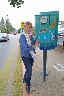 BELOVED KOI:  Marcie Hawthorne stands next to a utility box she painted in 2010 as part of San Luis Obispo's Box Art program. The city had plans to repaint several of the boxes, including this one, but changed course and will consider leaving some as they are. - PHOTO BY DYLAN HONEA-BAUMANN