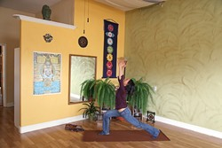 LET IT FLOW:  Silvia Suarez, new owner of the Holistic Movement Center in Morro Bay, demonstrates the warrior one yoga posture. Silvia won the studio through a contest and officially took over in January. - PHOTO BY DYLAN HONEA-BAUMANN