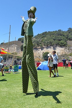 DOWN THE RABBIT HOLE:  The Mad Hatter moves through the crowd on stilts during the Central Coast Oyster and Music Fest on July 9. - PHOTO BY GLEN STARKEY