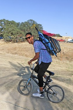 FAMOUS AMONG THE CROWD :  One of the main stage performers at LIB this year, Lafa Taylor, is one of the smart ones who brought his bike to get around the vast space that the festival is held on. - PHOTO BY DYLAN HONEA-BAUMANN